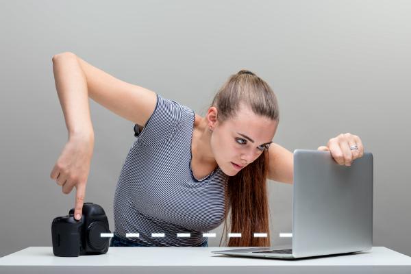 Frau überträgt Daten von einer Kamera auf den Laptop via Bluetooth