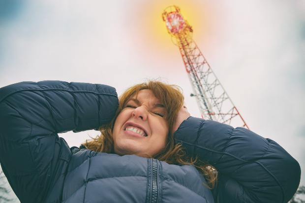 Elektrosensible Frau unter einem Funkmast