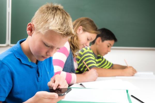 Schulkind benutzt heimlich das Handy im Unterricht