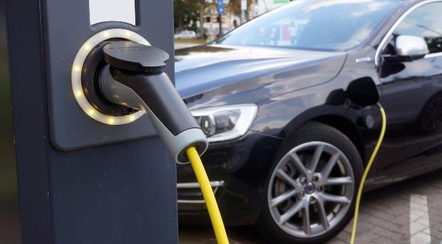 Elektroauto an einer Steckdose angeschlossen