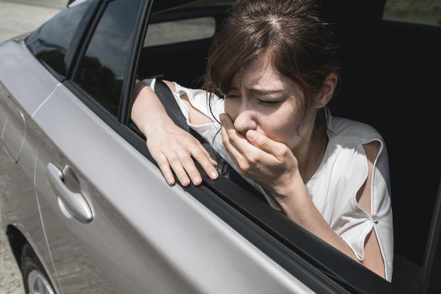 Frau mit Übelkeit im Auto - Elektrosmog im Auto