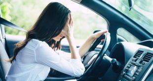 Frau im Auto mit Kopfschmerzen - Elektrosmog im Auto