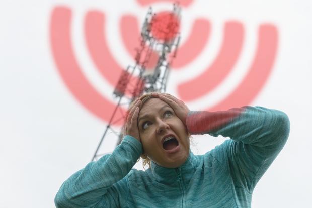 Frau steht unter einem 5G Mast
