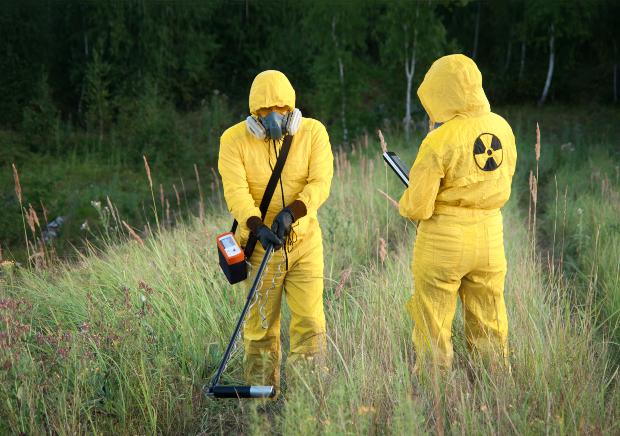 2 Männer ins Schutzanzügen messen Radioaktivität