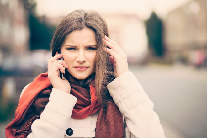 Junge Frau mit Handy hat Kopfschmerzen