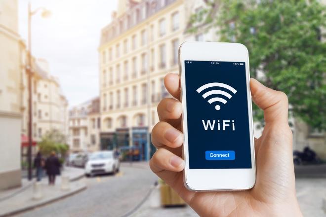 Person mit Handy in der Stadt - Handy zeigt WLAN an
