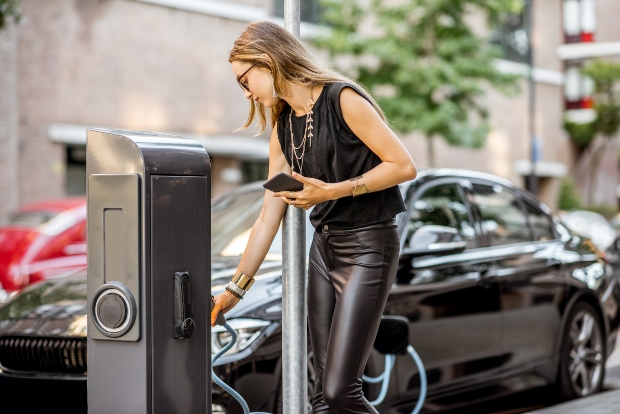 Frau lädt ihr Elektroauto auf, Handy in der Hand