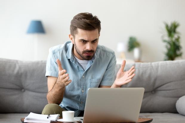 Mann sitzt verärgert vorm Laptop - Probleme bei der Powerline Communication
