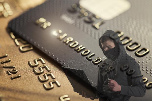 Kreditkarte in der Nahaufnahme; ein Betrüger mit Laptop im Vordergrund