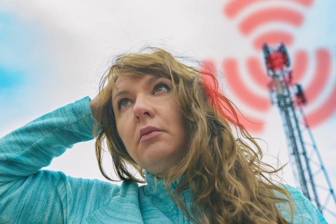Eine junge Frau fasst sich an den schmerzenden Kopf, im Hintergrund ein Funkmast