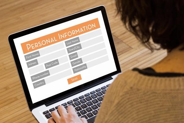 Frau am Laptop gibt persönliche Daten ein