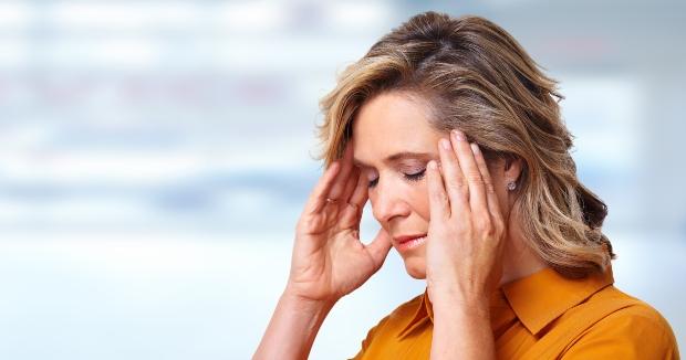 Frau mit Kopfschmerzen fasst sich an die Schläfen