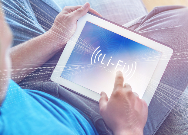 Mann sitzt mit Netbook im Schoß - verbunden per Lichtmodulation (Li-Fi)