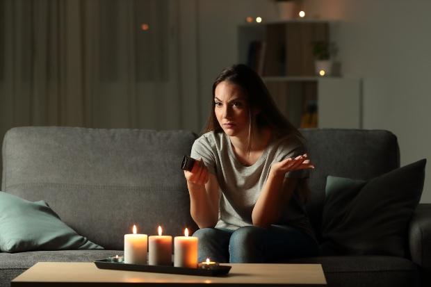Frau sitzt im Wohnzimmer ohne Strom - Risiken der neuen Smart Meter-Technik