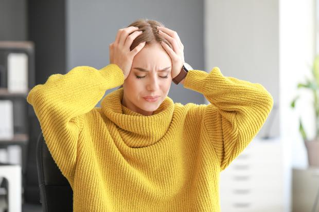 Frau hält sich vor Schmerzen die Hände an den Kopf